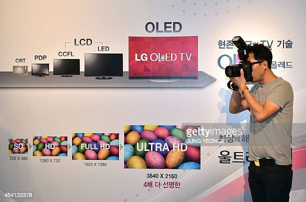 A photographer takes pictures in front of a signboard for LG's Ultra OLED TV during its unveiling ceremony in Seoul on August 25 2014 LG Electronics...