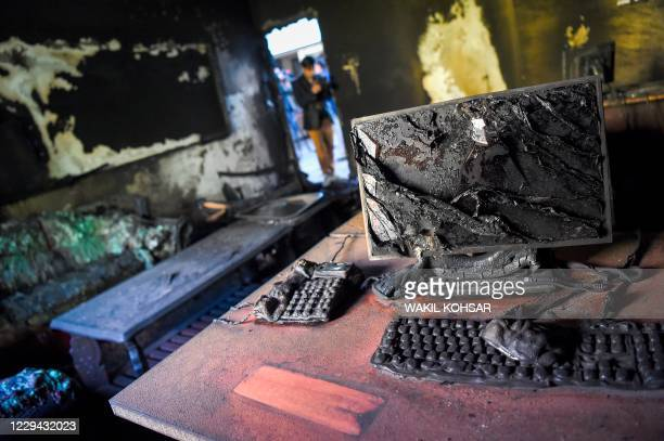 Photographer takes pictures inside a burned office of the National Legal Training center a day after gunmen stormed the university in Kabul on...