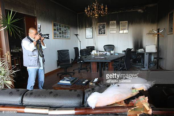 A photographer takes pictures of a damaged office in the Future movement's AlMustaqbal newspaper building after fire swept over one of its floors...