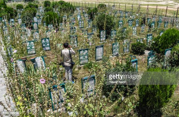 A photographer takes pictures of headstones on the graves at the martyrs graveyard during a curfew on the the first death anniversary of Burhan Wani...
