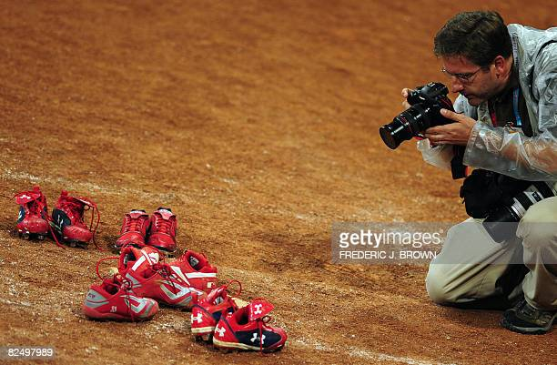 A photographer takes pictures of players' shoes left on home plate as a statement in regards to the sport of softball not being included as a sport...