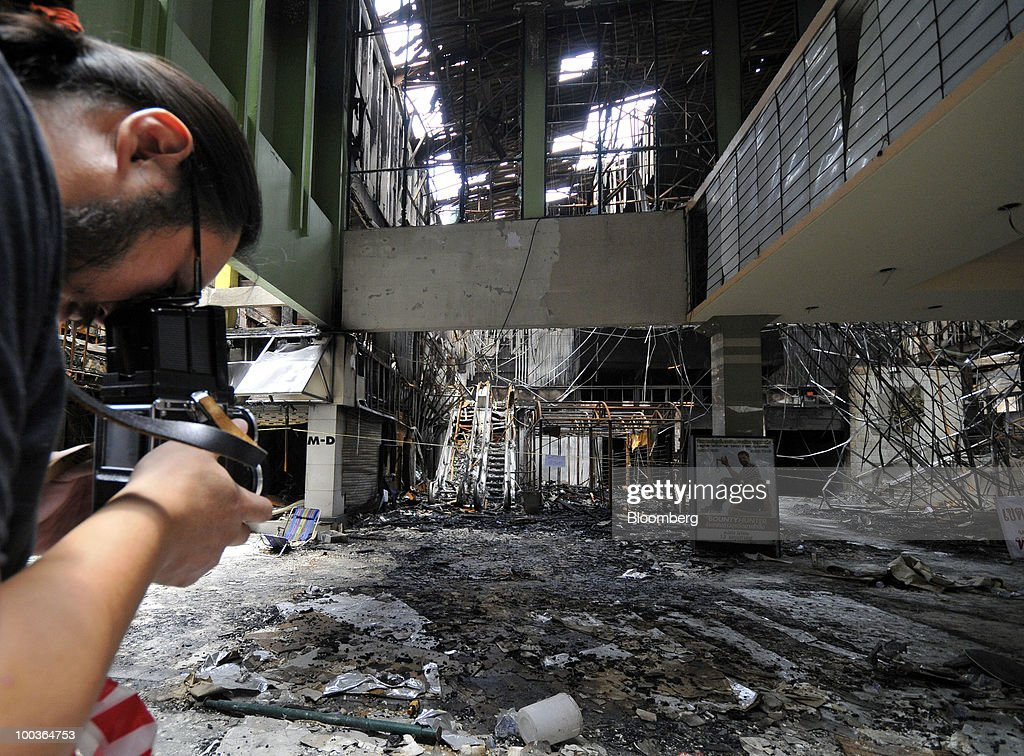 A photographer takes pictures of the burned remains of the Siam Cinema at the Siam Square shopping area in Bangkok, Thailand, on Monday, May 24, 2010. Efforts to clean up the city's commercial district gathered pace after the area was torched by rioting anti-government protesters. Photographer: Udo Weitz/Bloomberg via Getty Images