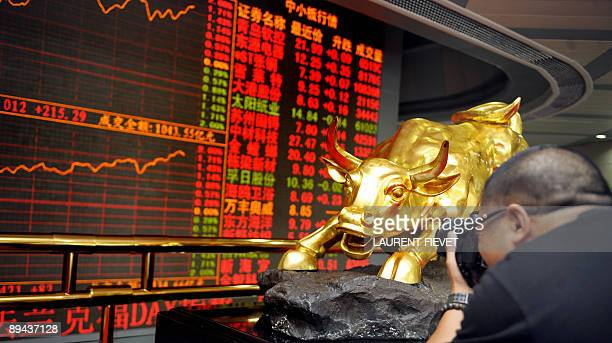 A photographer takes pictures of the Shenzhen Stock Exchange golden bull and index board in Shenzhen on July 27 2009 AFP PHOTO / LAURENT FIEVET