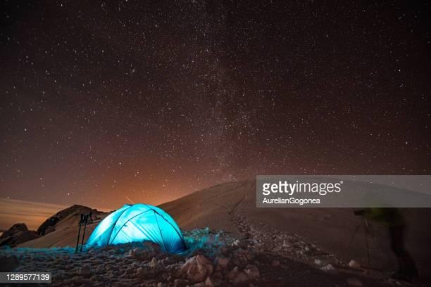 un photographe prenant une photo une tente allégée dans la nuit d'hiver avec le ciel plein d'étoiles - événement sportif d'hiver photos et images de collection