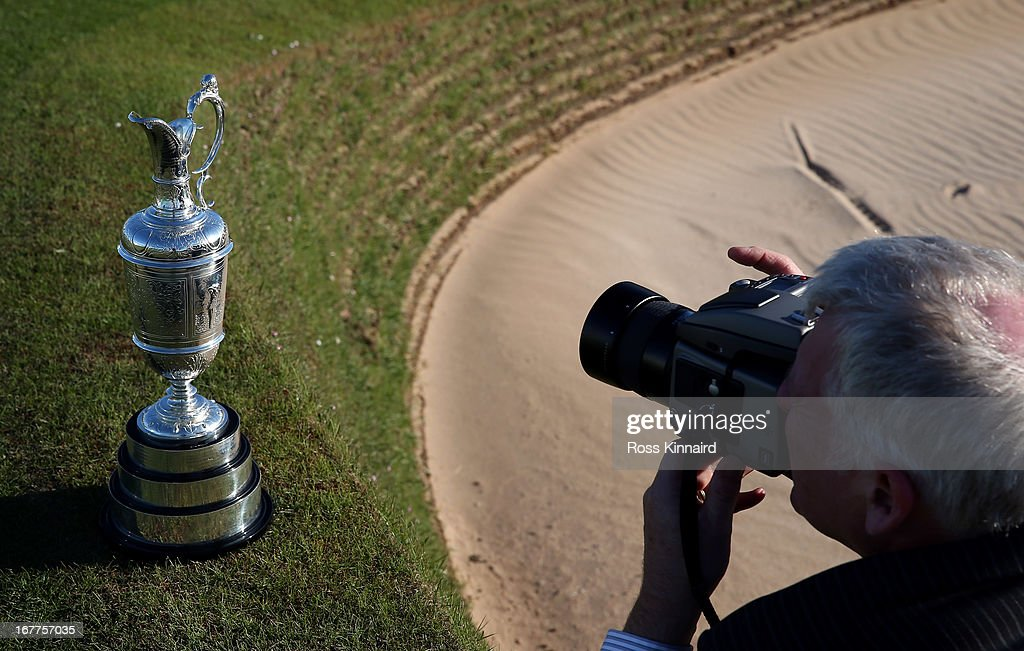 A photographer taking a picture of The Claret Jug trophy beside the 18th green in front of the clubhouse during The Open Championship media day at Muirfield on April 29, 2013 in Gullane, Scotland.