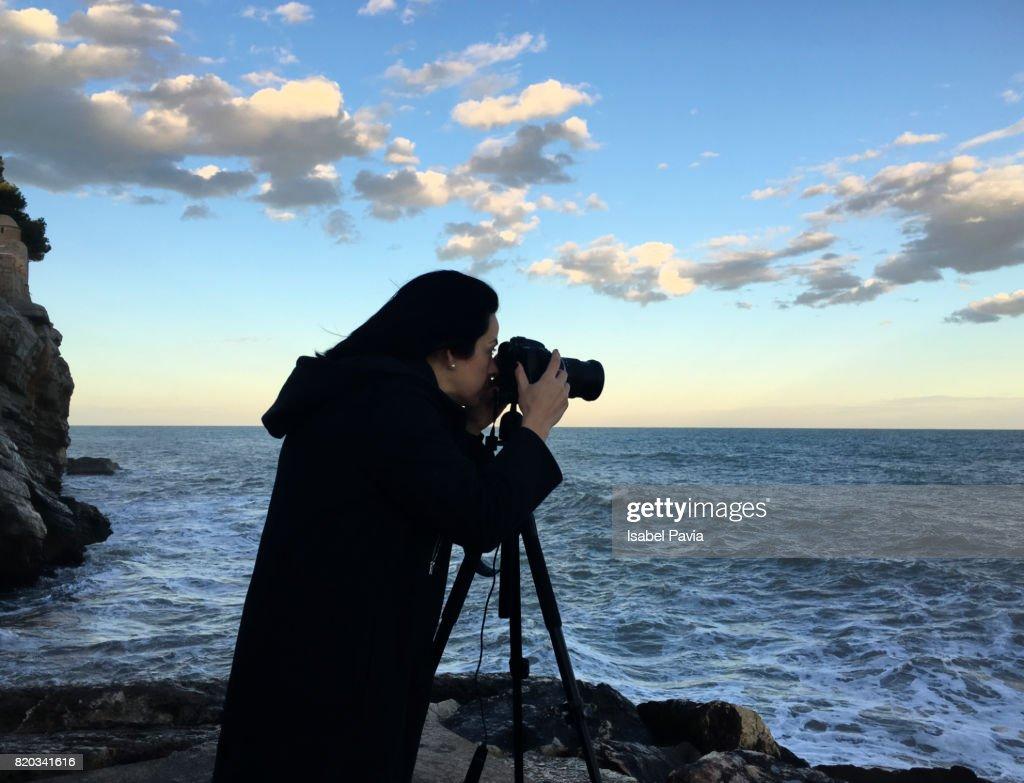 grapher Taking Sunset At Sea Stock