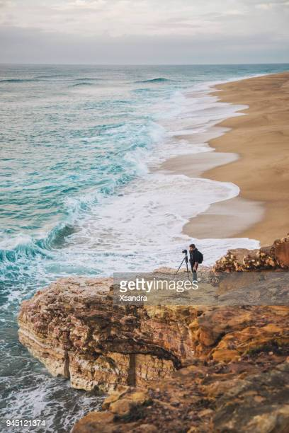 photographer taking photos at the cliff - leiria district stock photos and pictures