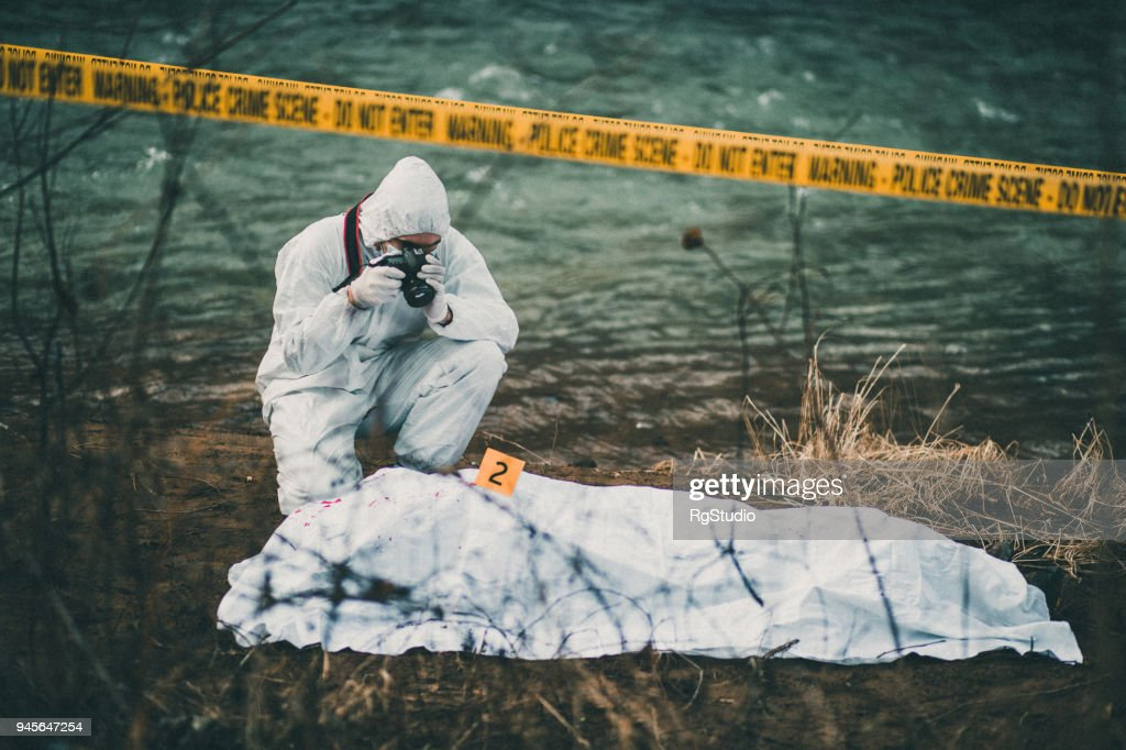 Photographer taking photos of crime scene by the river : Stock Photo