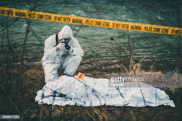 photographer taking photos of crime scene by the river - crimine foto e immagini stock