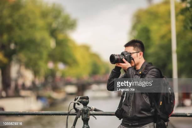 Photographer taking photos on bridge over Amsterdam canal, Netherlands