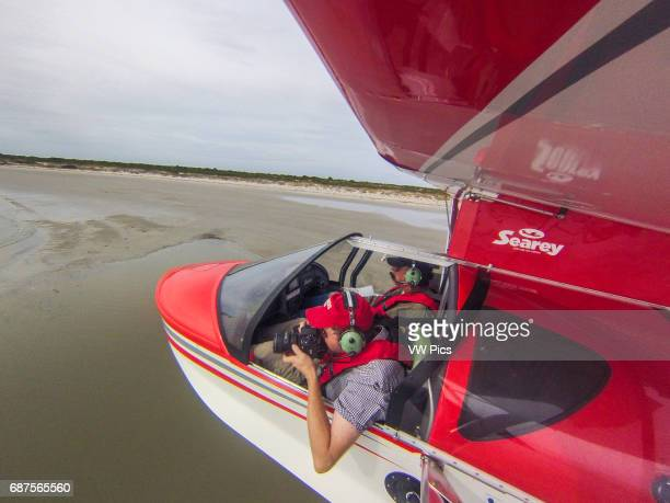 Photographer taking photos with camera out of seaplane window while flying in Southeastern USA