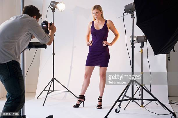 photographer taking picture of model in studio - fotosession stock-fotos und bilder