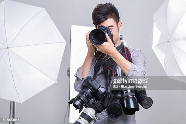 Photographer taking picture with many cameras hanging on his neck