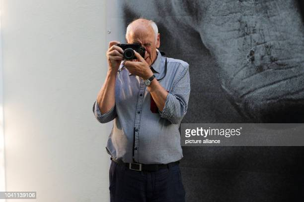Photographer Thomas Hoepker poses with his camera at the exhibition 'Muhammed Ali' in Berlin Germany 14 August 2015 Photo Paul Zinken/dpa | usage...