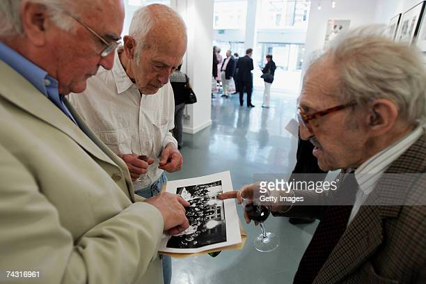 Photographer Thurston Hopkins looks at a photograph of a Picture Post social gathering with other guests at the Getty Images Gallery during the...