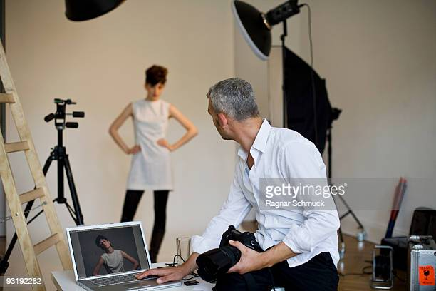 A photographer using a laptop on set of a fashion shoot