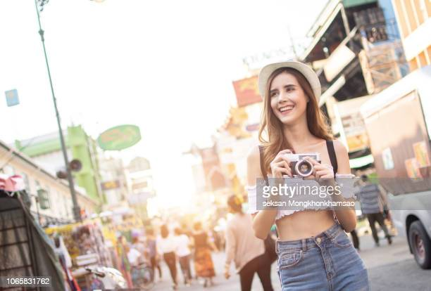 photographer using retro camera. tourist girl capturing the moment - 観光 ストックフォトと画像