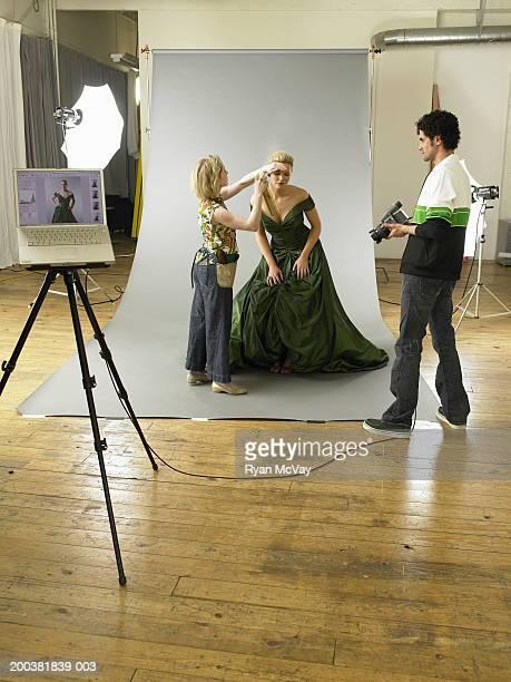 Photographer waiting as hairdresser styles female model's hair on set