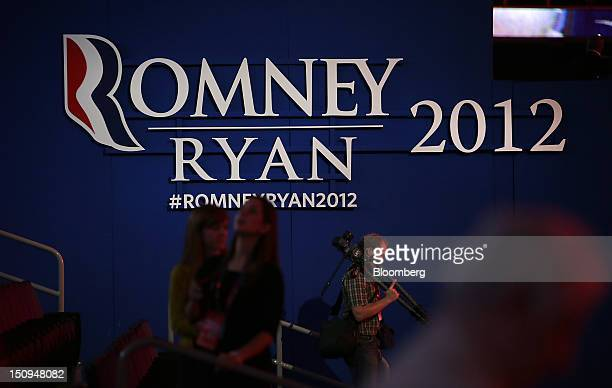 A photographer walks in front of a sign at the Republican National Convention in Tampa Florida US on Wednesday Aug 29 2012 Representative Paul Ryan...