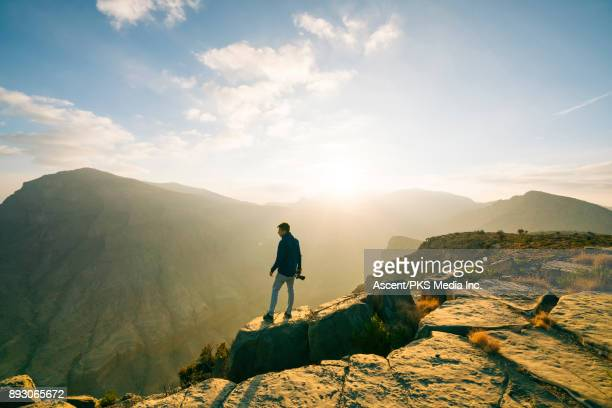 Photographer walks to edge of desert canyon, holding camera