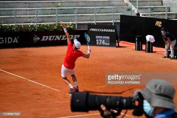 Photographer wearing a face mask takes photos as Norway's Casper Ruud serves to Italy's Matteo Berrettini during their quarter final match of the...