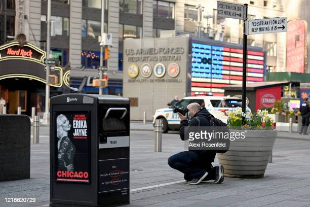 A photographer wearing a protective mask takes photos in an empty Times Square amid the coronavirus pandemic on April 12 2020 in New York City United...