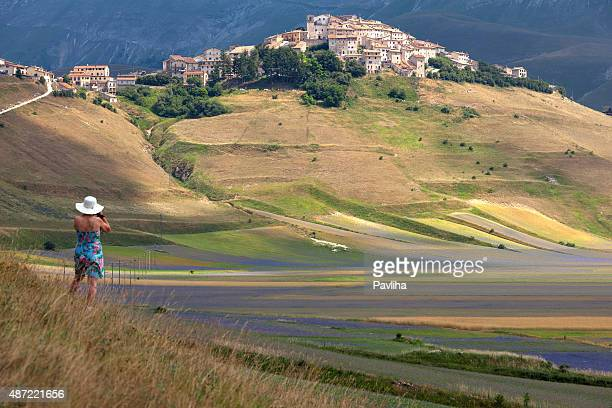 photographer wearing flower pattern dress abd white hat, castelluccio, italy - castelluccio stock pictures, royalty-free photos & images