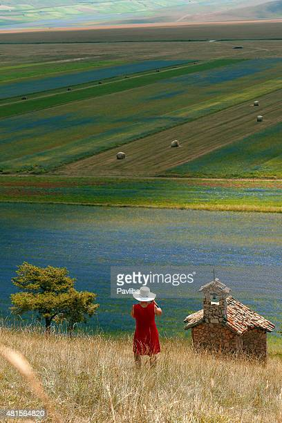 photographer wearing red dress abd white hat near castelluccio, italy - castelluccio stock photos and pictures