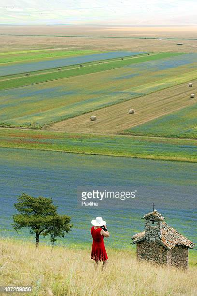 photographer wearing red dress abd white hat near castelluccio, italy - castelluccio stock pictures, royalty-free photos & images
