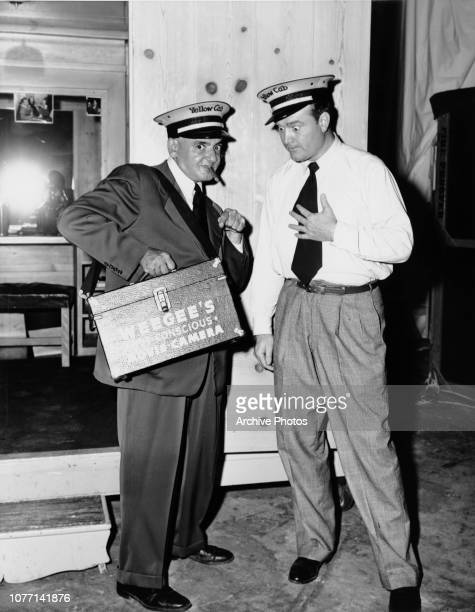 Photographer Weegee , aka Arthur Fellig, shows 'Weegee's Sub Conscious Movie Camera' to actor Red Skelton on the set of the MGM film 'The Yellow Cab...