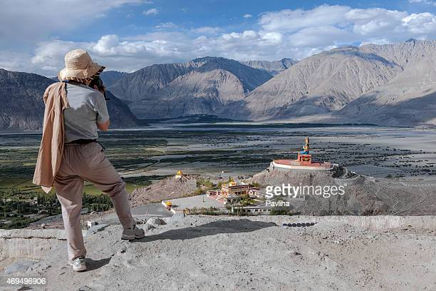 Photographer with a hat, photographs Buddhist shrine  , Stupas Nubra valley
