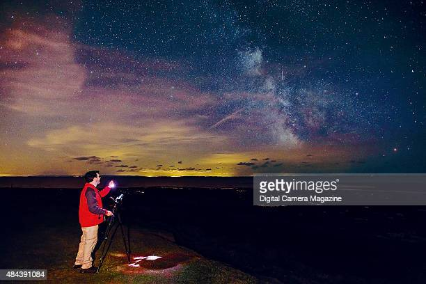 A photographer with a tripodmounted DSLR camera taking longexposure pictures of stars at night on August 23 2014