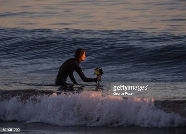 A photographer with a waterproof camera takes pictures in the surf at sunset on December 1 in Refugio State Park California Because of its close...