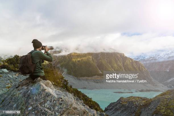 photographer with backpack photographing on rock against cloudy sky - fotografo foto e immagini stock