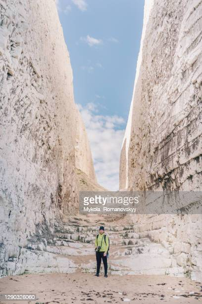 photographer with camera and tripod attached to backpack, standing in front of the cliffs. - north stock pictures, royalty-free photos & images