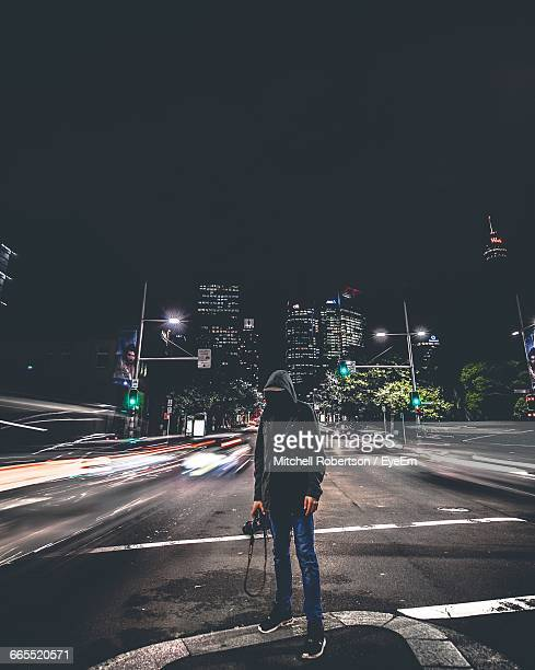 Photographer With Camera Standing Amidst Light Trails On Street At Night