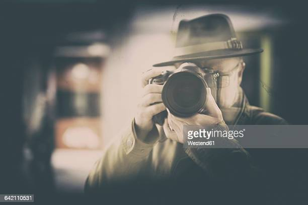 Photographer with hat mirrored in window display