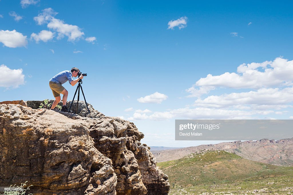 Photographer with tripod on a mountain top : Stock Photo