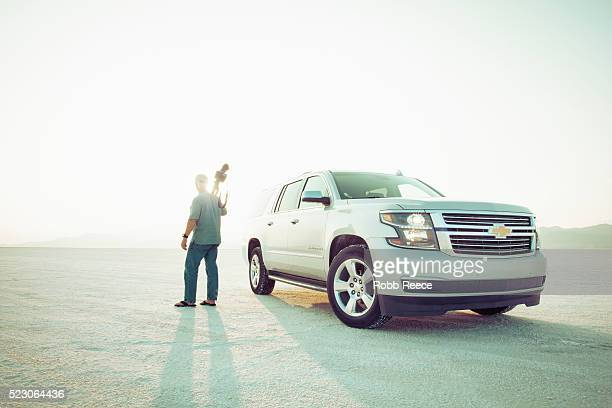 a photographer with tripod standing with a chevrolet suburban at bonneville salt flats, utah - robb reece stock pictures, royalty-free photos & images