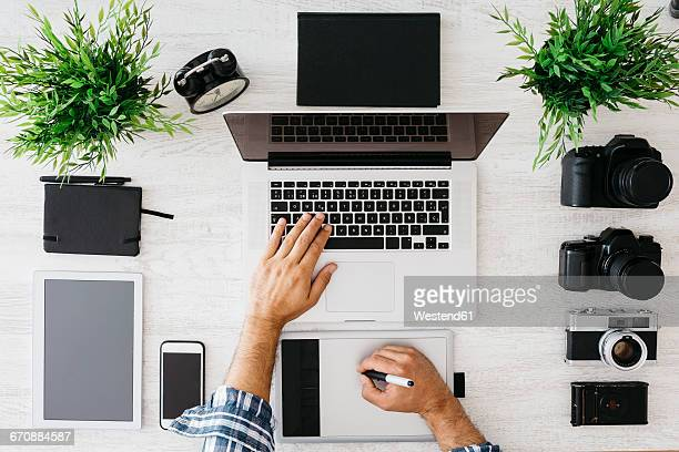Photographer working at desk with laptop, top view