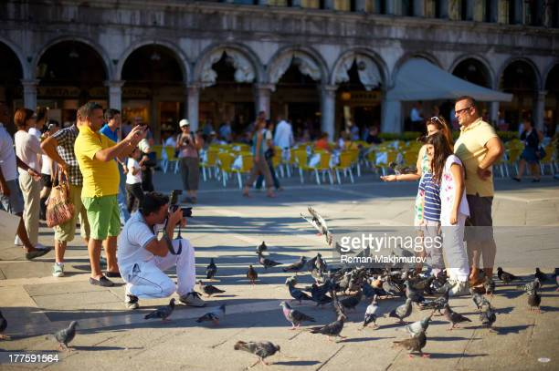 CONTENT] Photographer working for tourists on Piazza San Marco Tourists surrounded by pigeons