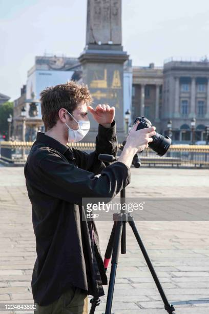 Photographer working Place de la Concorde with surgical protective mask having a derogatory certificate to work, Europe, France, Paris.