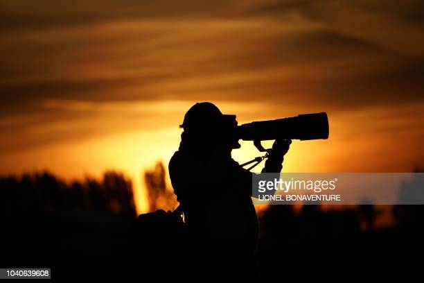 A photographer works at sunrise ahead of a practice session ahead of the 42nd Ryder Cup at Le Golf National Course at SaintQuentinenYvelines...