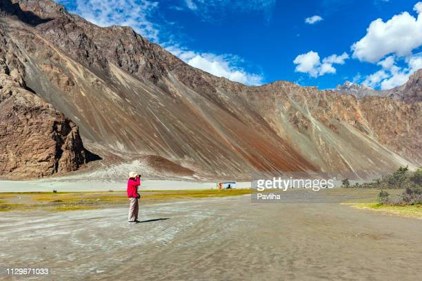 a photographer works in a photo in the nubra valley,jammu and kashmir, ladakh region, tibet, india - geographical locations stock pictures, royalty-free photos & images