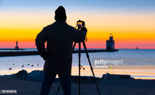 photographer works in cold lake michigan march twilight. - march month stock pictures, royalty-free photos & images
