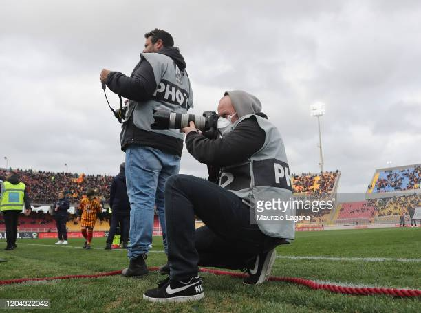 A photographer works with a protective mask during the Serie A match between US Lecce and Atalanta BC at Stadio Via del Mare on March 1 2020 in Lecce...