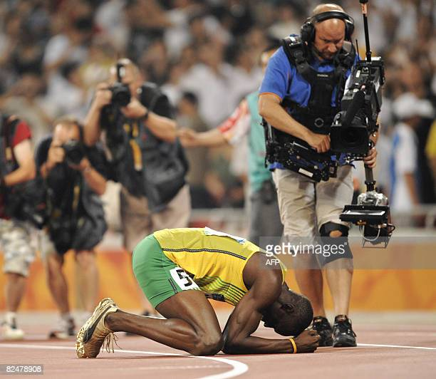 Photographers and a cameraman film Jamaica's Usain Bolt as he celebrates winning the men's 200m final at the 'Bird's Nest' National Stadium during...