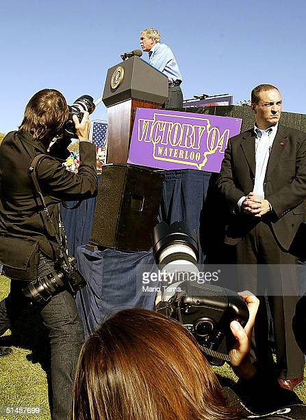 Photographers and a Secret Service officer look on as US President George W Bush speaks to supporters at a Victory 2004 rally October 9 2004 in...