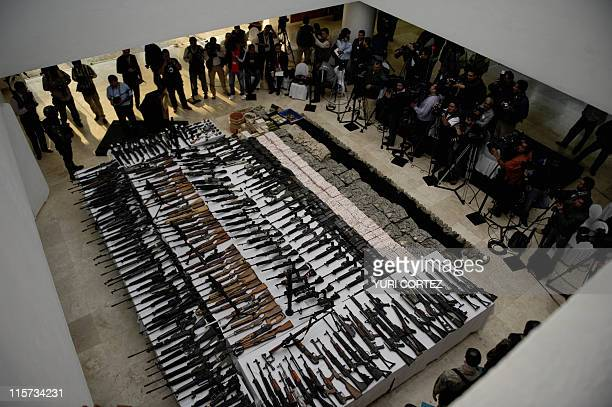 Photographers and cameramen take images of different kinds of firearms cocaine and military uniforms seized to alleged members of the Zetas drug...