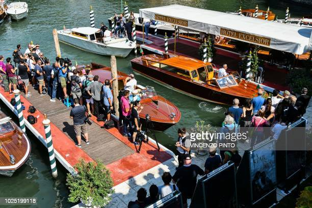 Photographers and festival goers gather at a pier were actors arrive by boat at the Excelsior hotel on August 30, 2018 during the 75th Venice Film...